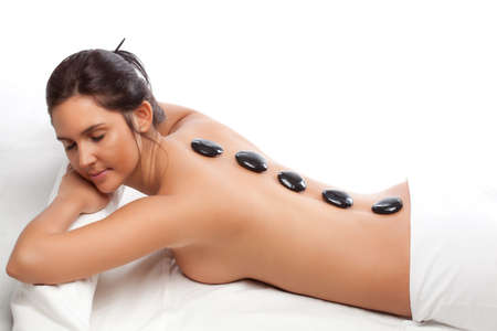 hot rock therapy: pretty woman receiving a therapy with hot stones in spa center over white
