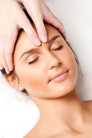 gezichtsbehandeling: mooie vrouw gezicht massage, close-up foto ontvangen