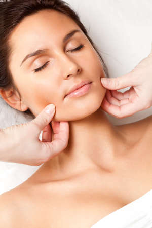 pretty woman receiving face massage, closeup photo photo