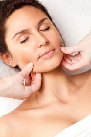 facial massage: pretty woman receiving face massage, closeup photo