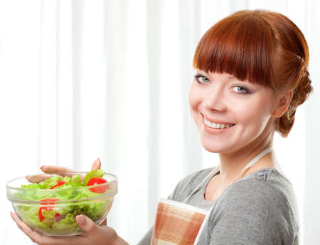 ginger housewife holding glass plate with salad over white photo