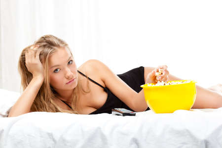 woman on bed eating popcorn, watching tv photo