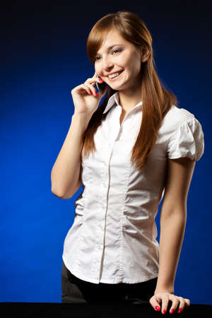 businesswoman with mobile phone over blue background photo