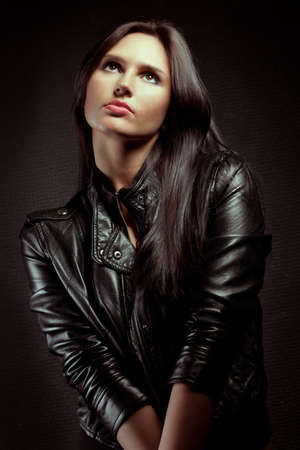 beautiful sexual  woman portrait wearing leather jacket near wall photo