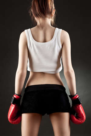 female boxer: young woman wearing red boxer gloves back view