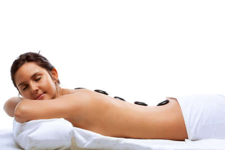 hot stone massage: pretty woman receiving a therapy with hot stones in spa center over white