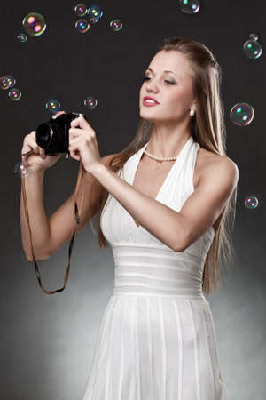 blonde woman with vintage camera over dark background photo