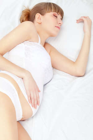 beautiful pregnant sleeping woman on white bed photo