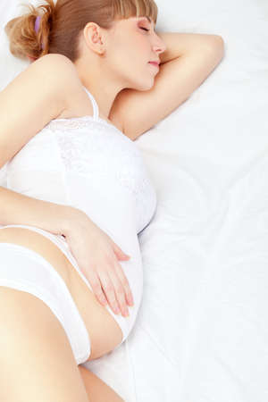 lying on the stomach: beautiful pregnant sleeping woman on white bed Stock Photo