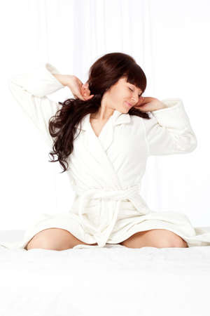 beautiful woman wearing bathrobe sitting on the bed photo