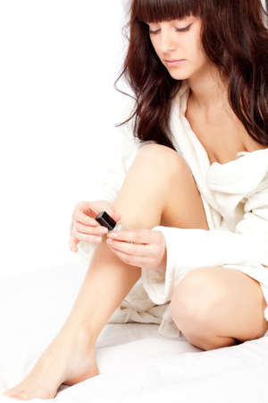 woman polish nails sitting on the bed photo