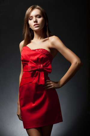 chatoyant: beautiful woman wearing red dress over dark background