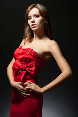 chatoyant: beautiful woman wearing red dress over dark background