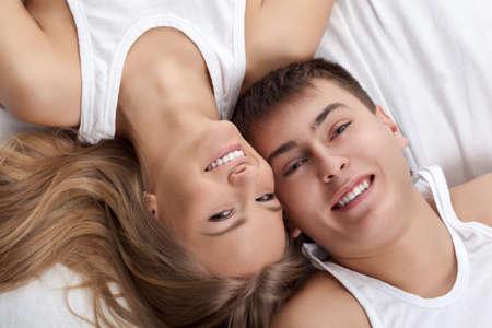 salud sexual: pareja adulta joven tumbado en la cama blanca Foto de archivo