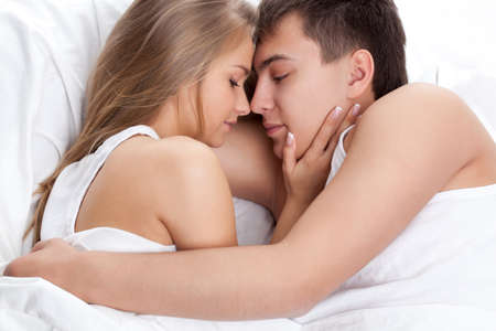 young adult couple lying on white bed