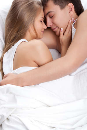 romance bed: young adult couple lying on white bed
