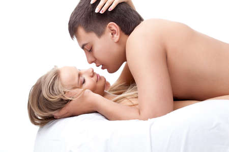 lovers in bed: young adult couple lying on white bed