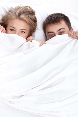 enamorados en la cama: pareja adulta joven tumbado en la cama blanca Foto de archivo