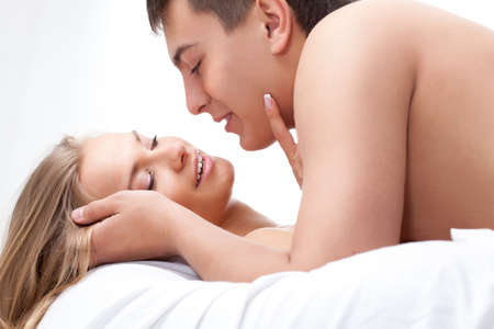 young adult couple lying on white bed photo