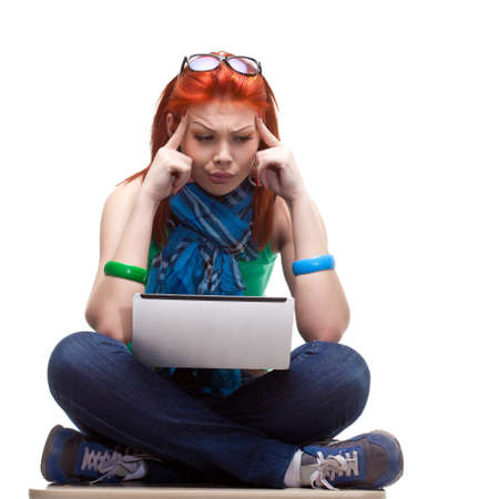 seriously: happy girl sitting with laptop over white Stock Photo