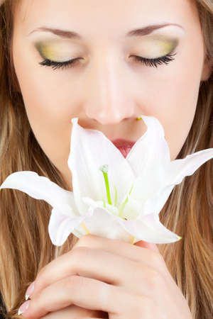closeup woman with closed eyes holding lily photo
