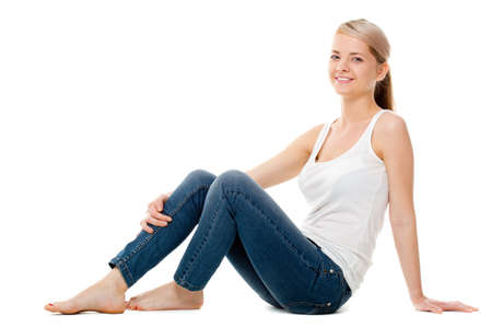 women in jeans: beautiful woman sitting on the floor over white Stock Photo