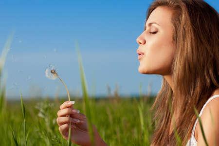 viento soplando: hermosa mujer que sopla a dandelio en campo verde Foto de archivo