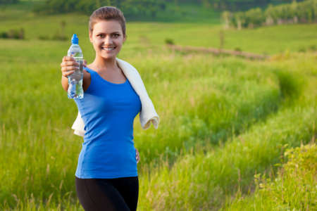 sport woman holding water on field