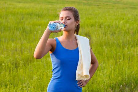sport woman drinking water on field photo