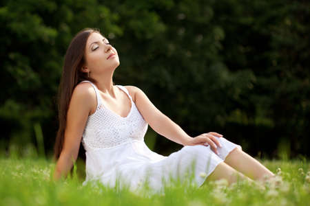 woman wearing white dress sitting on grass in park Stock Photo - 10544748