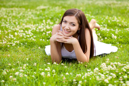 woman wearing white dress laying on grass in park Stock Photo - 10544754