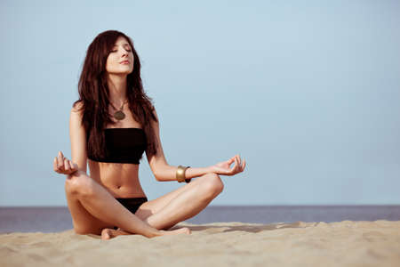 woman sitting on sand in lotus pose photo