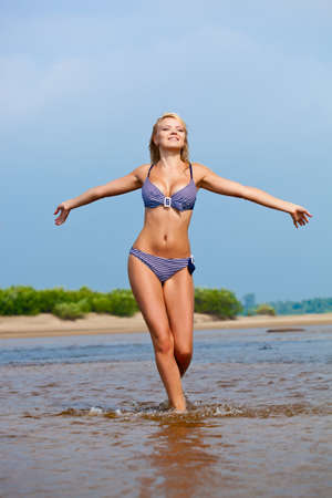 young bikini: beautiful woman walking on water wearing bikini