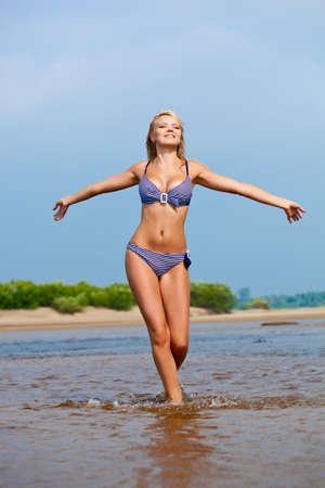 bikini bleu: belle femme marchant sur l'eau portant bikini
