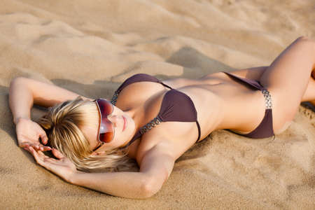 girl lying: beautiful blonde woman on beach wearing brown bikini Stock Photo