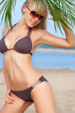blue bikini: beautiful blonde woman on beach wearing brown bikini Stock Photo