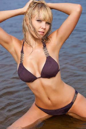 beautiful blonde woman in water wearing brown bikini photo