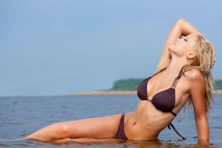 blonde bikini: beautiful blonde woman in water wearing brown bikini