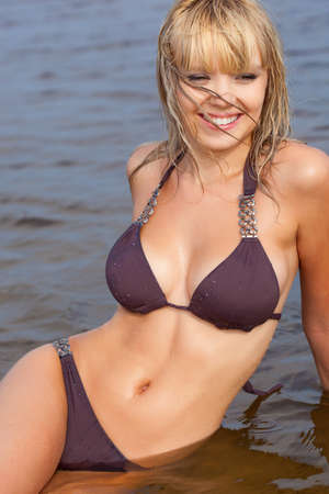 swimsuit: beautiful blonde woman in water wearing brown bikini