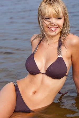 badpak: mooie blonde vrouw in het water draagt bruine bikini