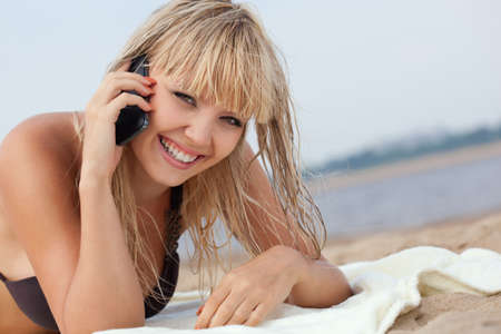 mobile telephone: beautiful blonde woman on beach calling by phone Stock Photo