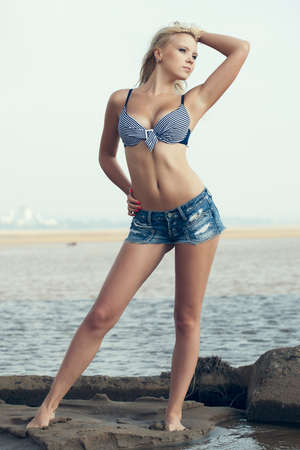 blonde bikini: beautiful blonde woman standing on sand