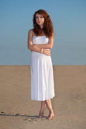 red-haired beautiful woman walking on sand wearing white dress photo