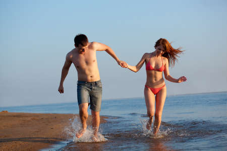 young adult happy couple running on beach photo