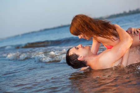 red haired: young adult happy couple couple laying water Stock Photo