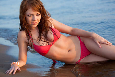 red haired woman: beautiful red-haired  woman wearing bikini on beach