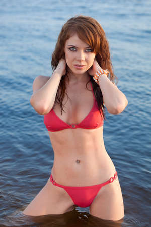 red haired girl: beautiful red-haired  woman wearing bikini on beach