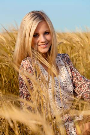 cultivo de trigo: hermosa mujer sentada en el campo de trigo