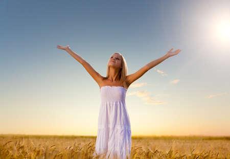mujer pensativa: hermosa mujer caminando en campo de trigo antes de la puesta del sol