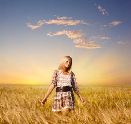 wheat grass: beautiful woman walking on wheat field before sunset